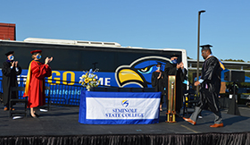 A student crosses the stage as President Dr. Georgia Lorenz claps during the drive-thru, hybrid graduation in Dec. 2020