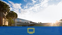 The Sanford/Lake Mary Campus building L. The sun is setting. There is a blue rectangle with a desktop icon at the bottom.