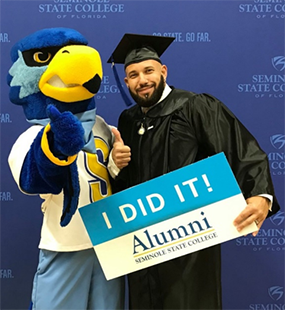 Student in a black graduation robe posing with Rally the Raider mascot holding a sign which says 'I Did It! Alumni Seminole State College'