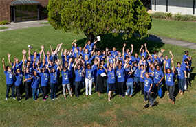 Group of students standing in the grass outside of a building, wearing blue shirts, waiving to the camera with their arms high in the air.