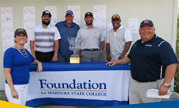 Foundation Dream Cup 2020 Golf Tournment winners posing with trophy at a table with Seminole State College President Dr. Georgia Lorenz and John Gyllin, Vice President, Resource and Economic Development and Foundation Executive Director.