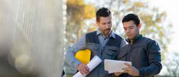 jobsite architect and worker reviewing plans on a jobsite